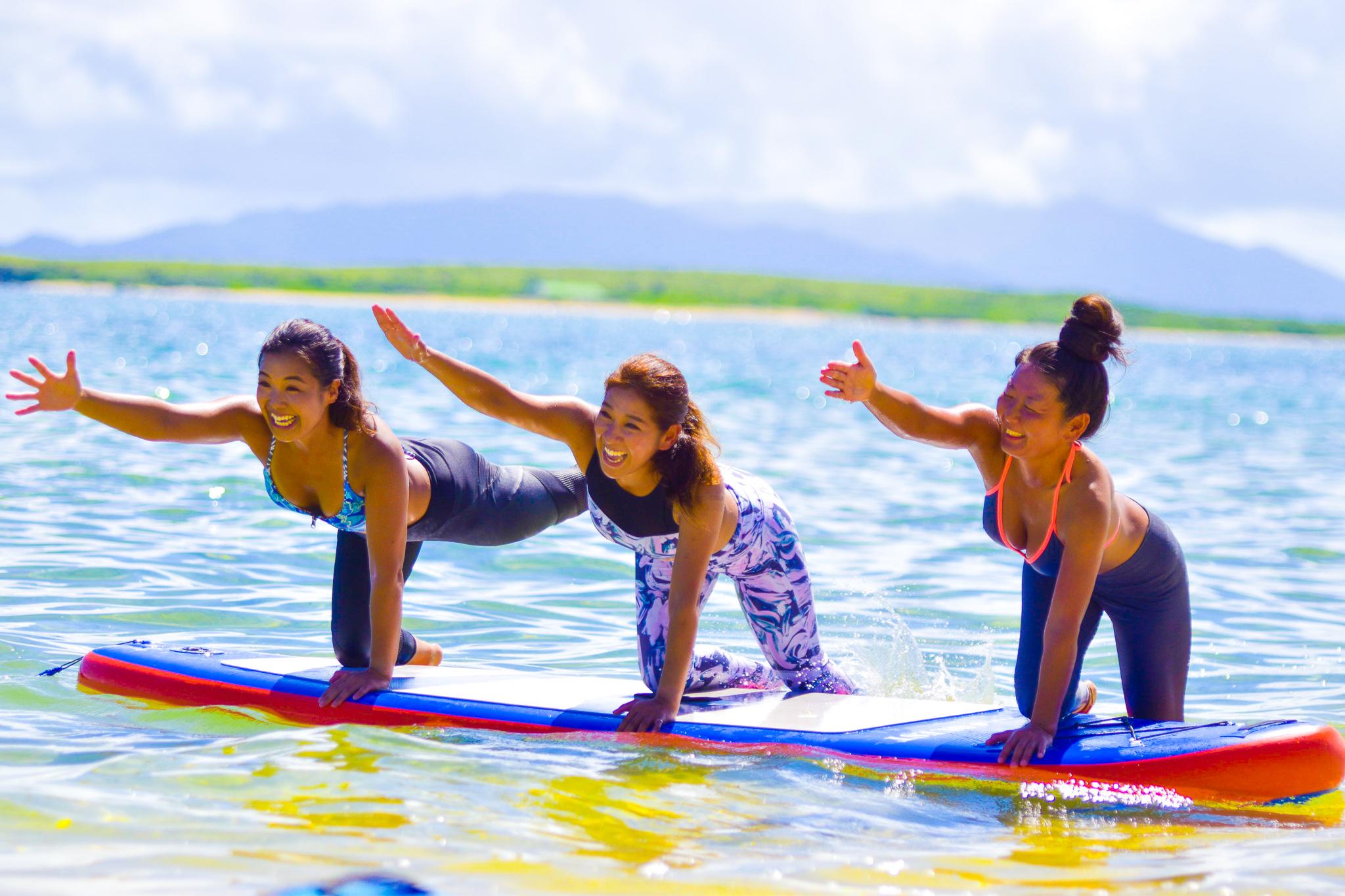 ボードの上でヨガのポーズをとる女性達